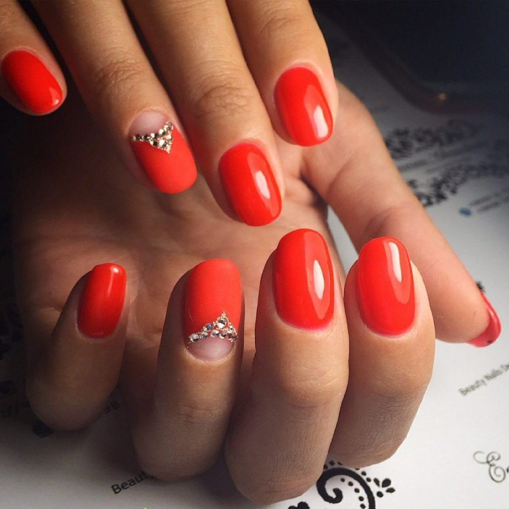 Яркий красный маникюр с прозрачной лункой на безымянном пальце, украшенной стразами в виде треугольника