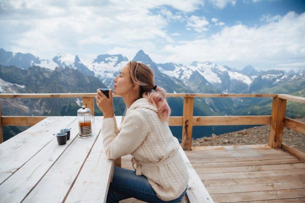 Девушка сидит за столом на фоне гор и пьет чай