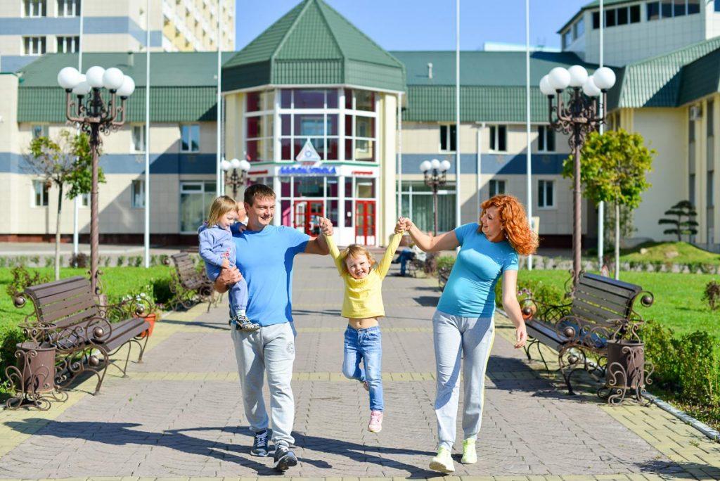 Пара с детьми на фоне санатория