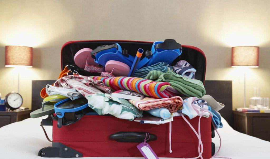 Набитый чемодан на кровати