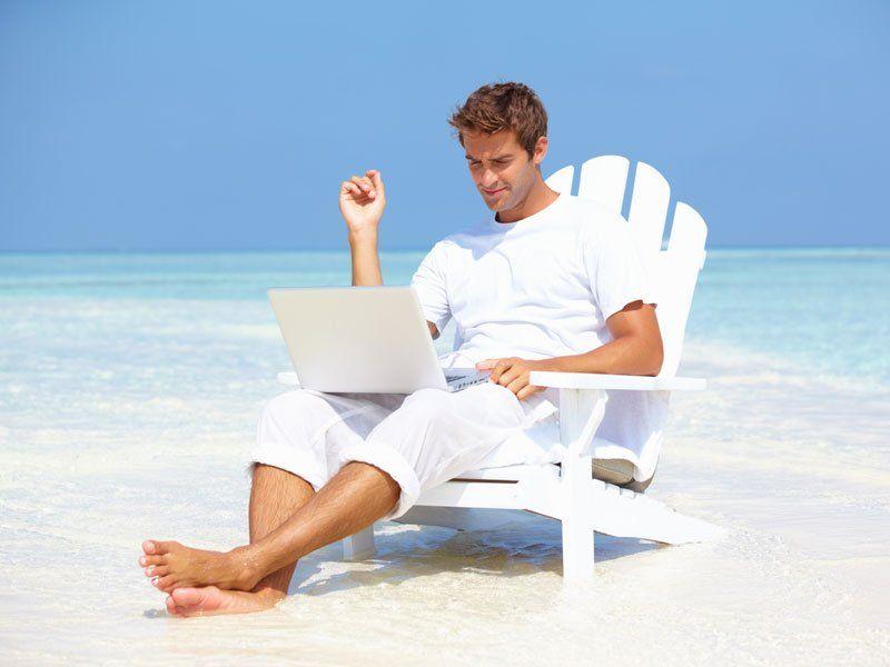 Мужчина в белом шезлонге и с ноутбуком на пляже