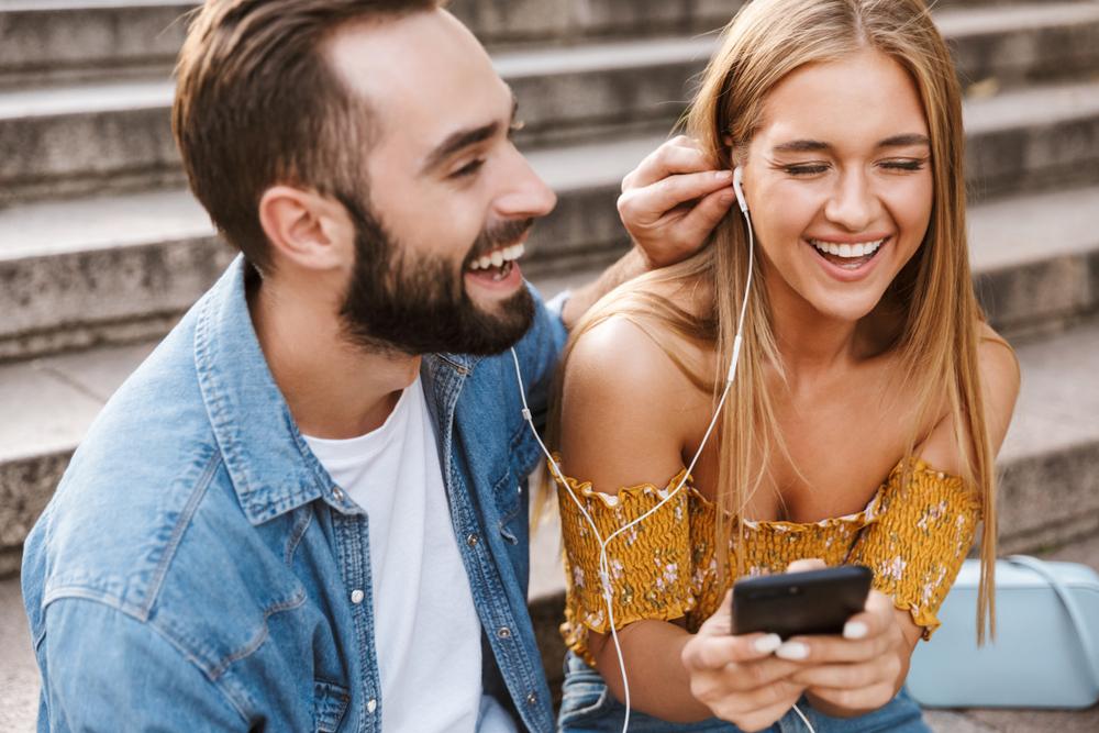 Парень и девушка вместе слушают музыку в наушниках