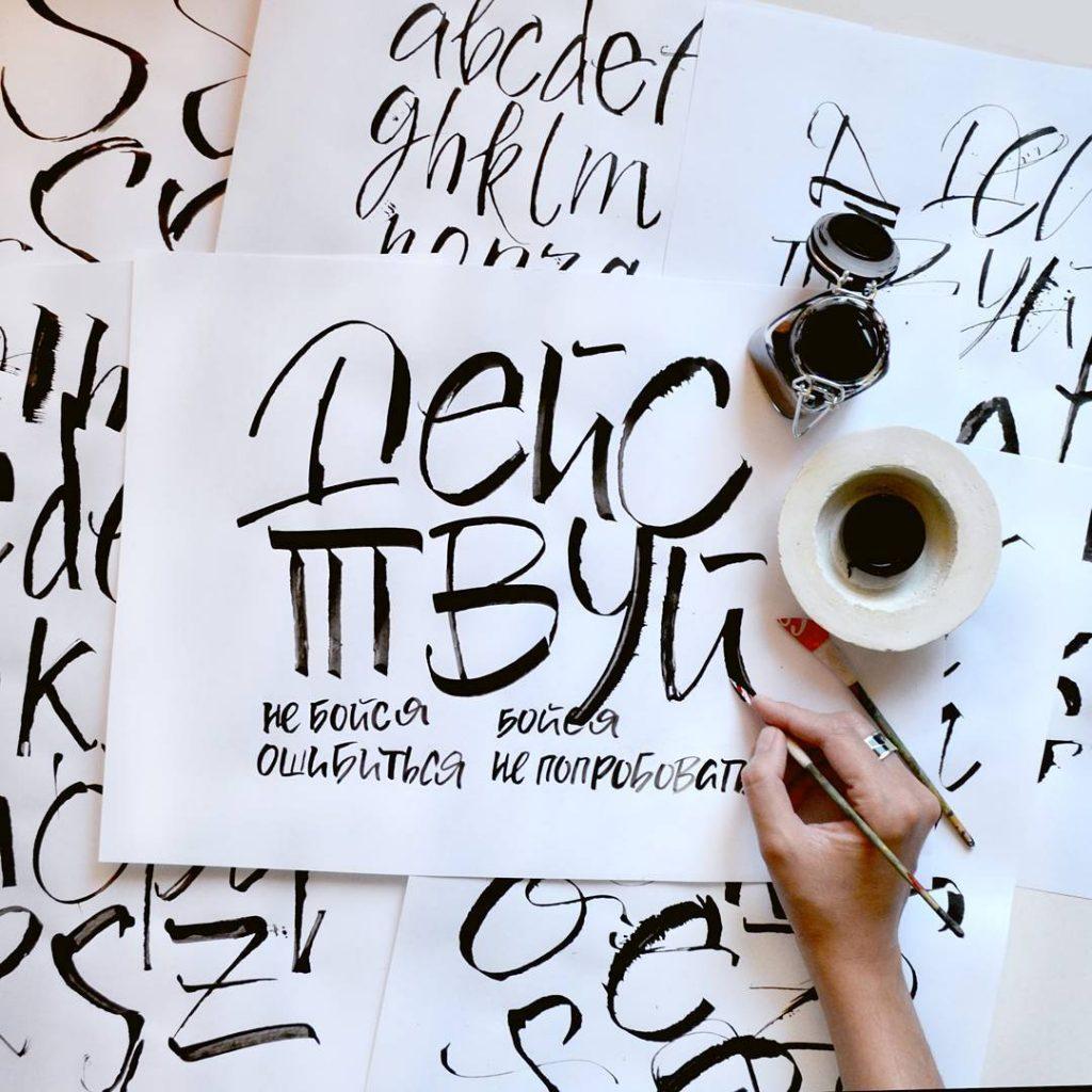Крупным планом рука, рисующая пером надпись на бумаге