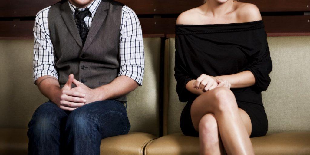 Мужчина и женщина сидят рядом на диване в напряженных позах