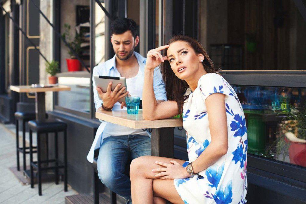 Девушка скучает, пока парень смотрит в свой планшет