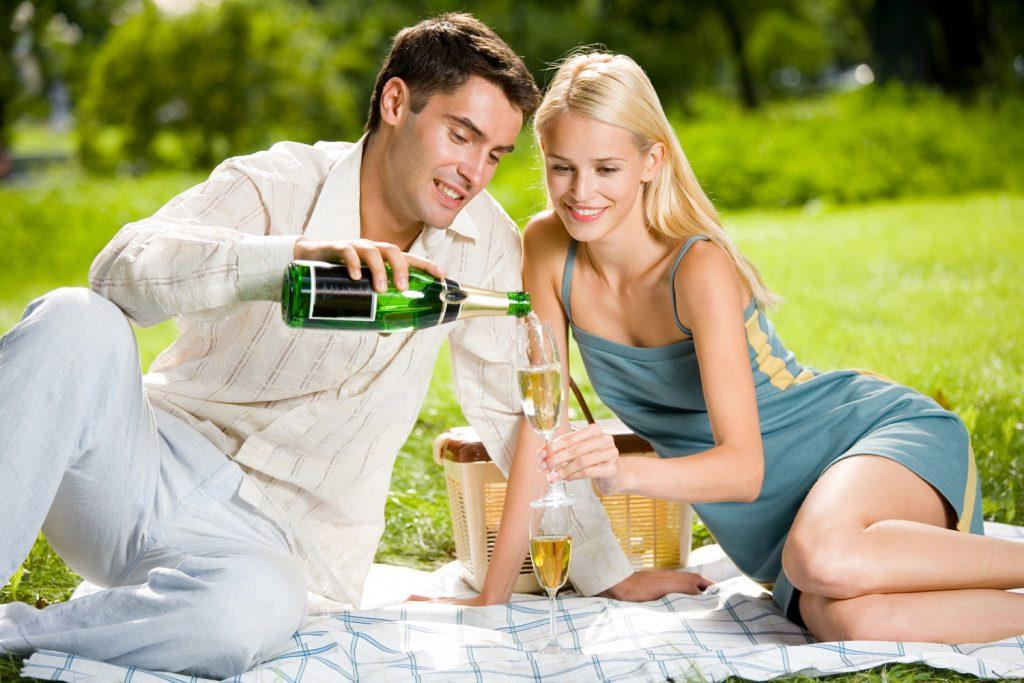 Парень и девушка на пикнике пьют вино