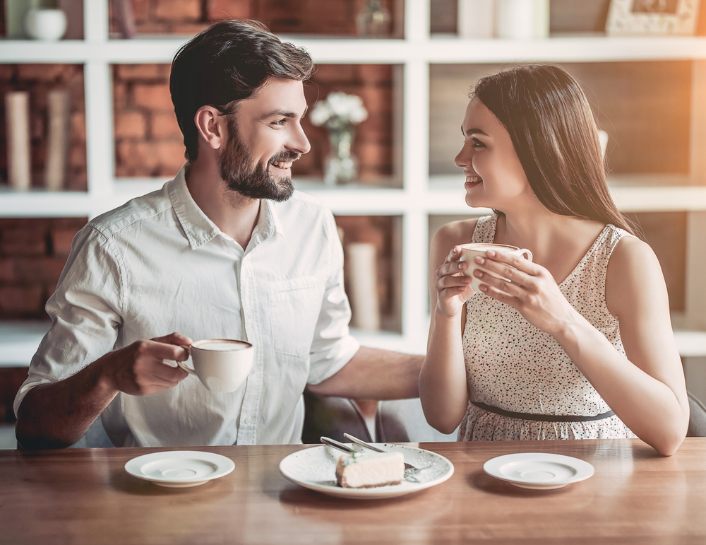 Пара пьет кофе, улыбаясь друг другу