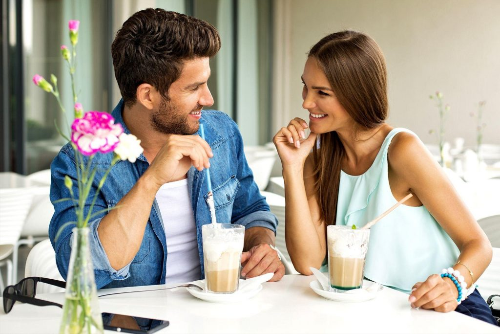 Парень и девушка пьют кофе и улыбаются друг другу