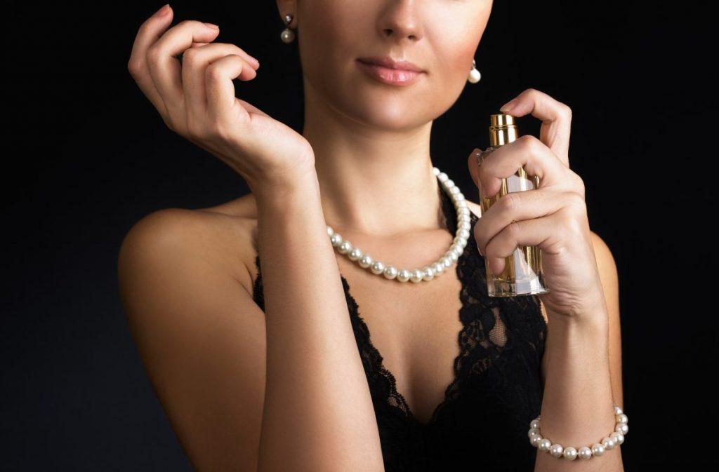 Жінка розпилює парфуми на зап'ястя