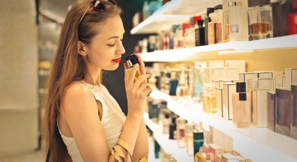 Дівчина тестує аромат у магазині парфумерії