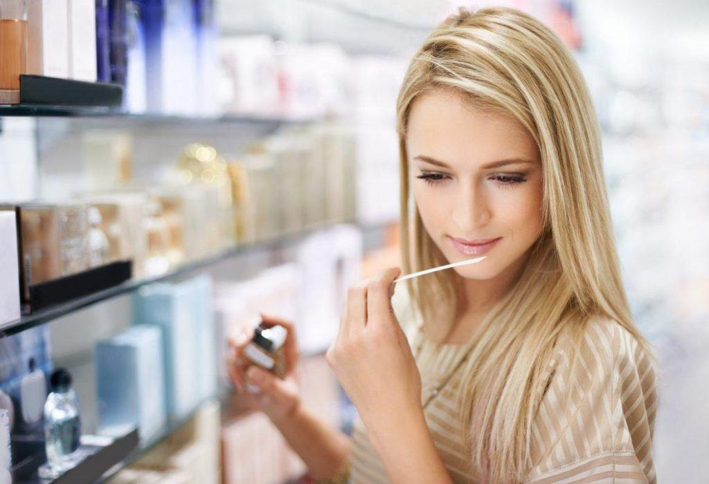 Жінка тримає тестер з ароматом
