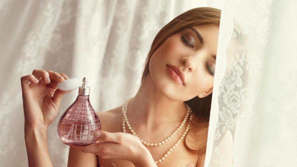 Жінка розпилює на себе парфуми