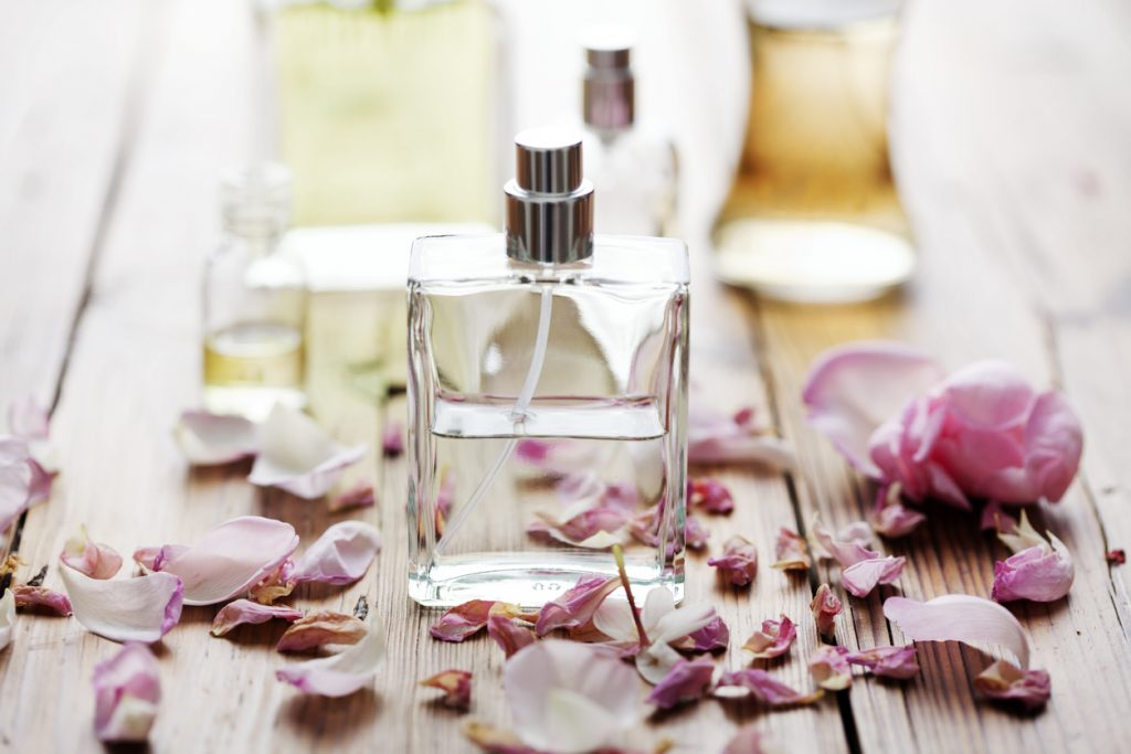 Один флакон з парфумами на тлі інших, а також розсипаних квіткових пелюстків