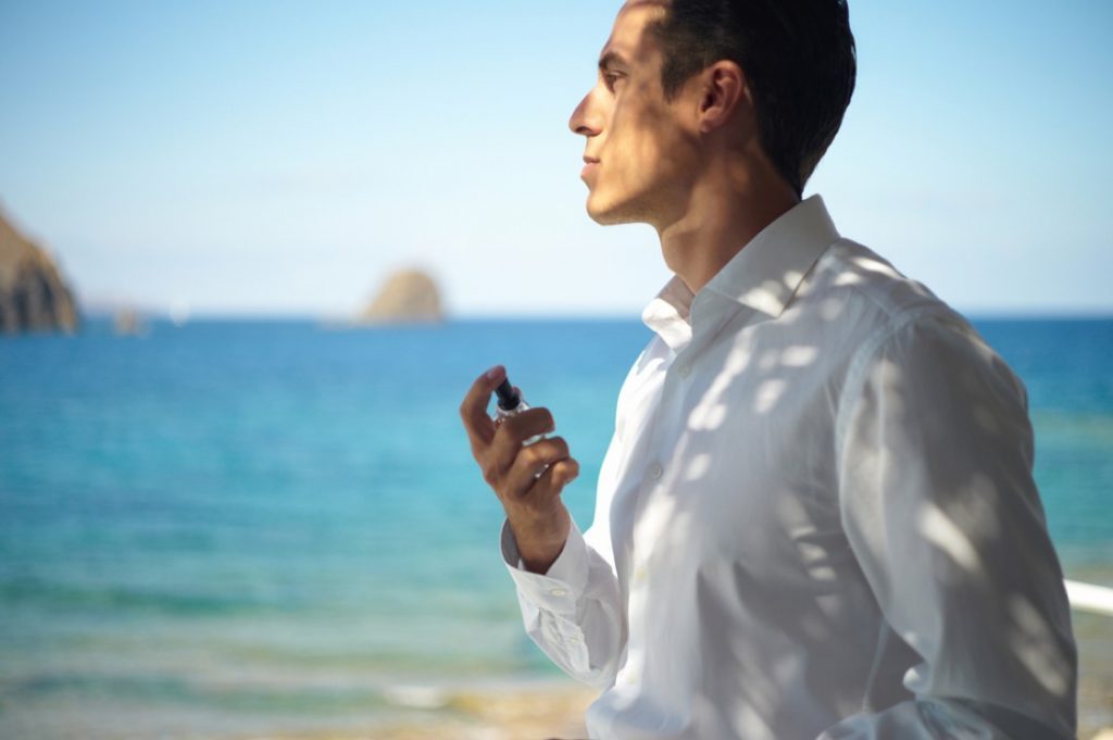 Чоловік розпилює на себе парфуми на тлі моря