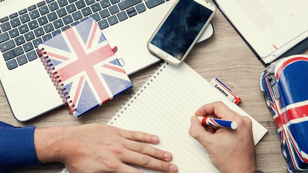 Крупным планом рука, которая держит ручку, тетрадь, блокнот и пенал с британским флагом, смартфон и ноутбук