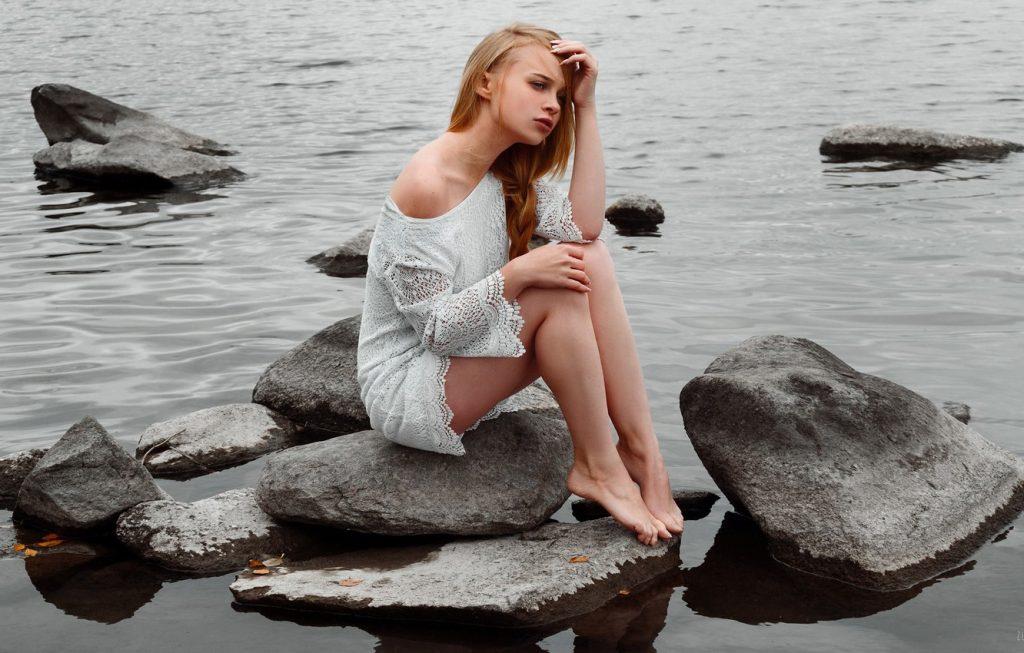 дівчина сидить на камені