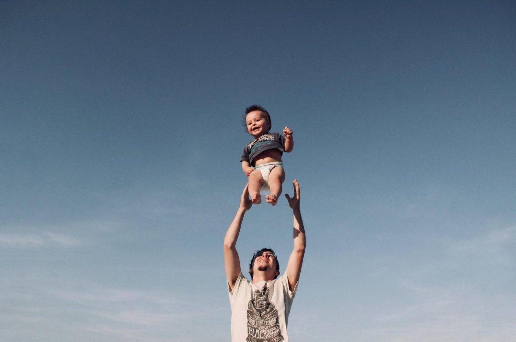 тато підкидує малюка