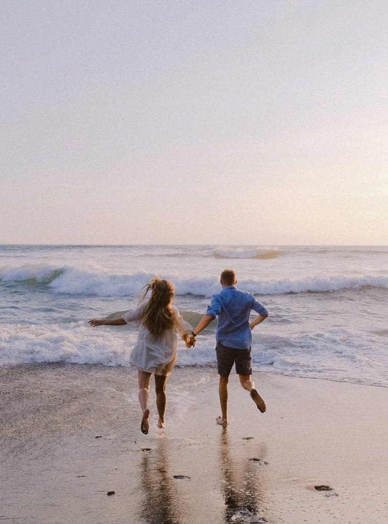 пара біжить босоніж по берегу